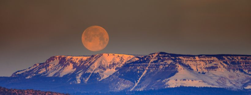 A photograph by Andrea Reiman of the moon setting over a plateau.