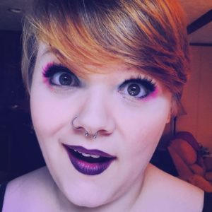 a selfie of the author wearing pink, blue, and purple eyeshadow and purple lipstick